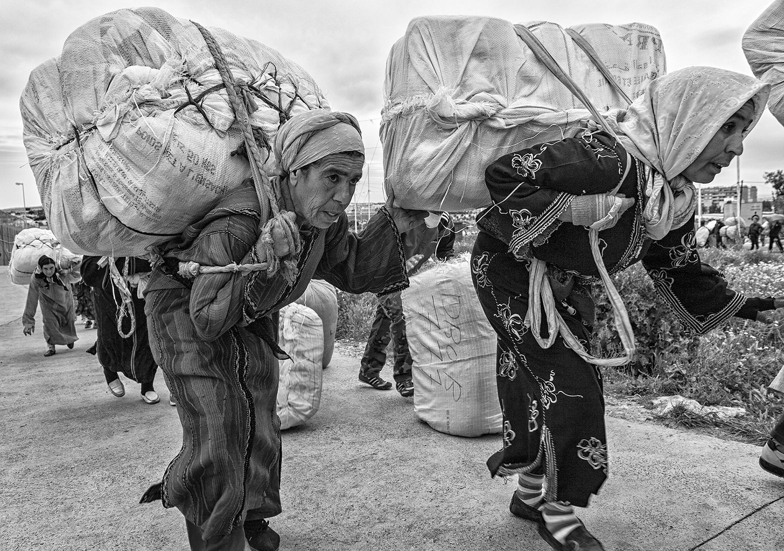 Two elderly women walk toward the Melilla crossing point carrying on their backs heavy bales of merchandise. Usually this transport is performed from some warehouses located several kilometers away from the border. Melilla. Spain