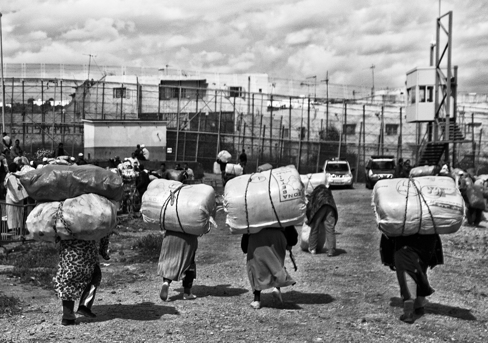 Four women walk towards the border with heavy loads on their backs. Melilla