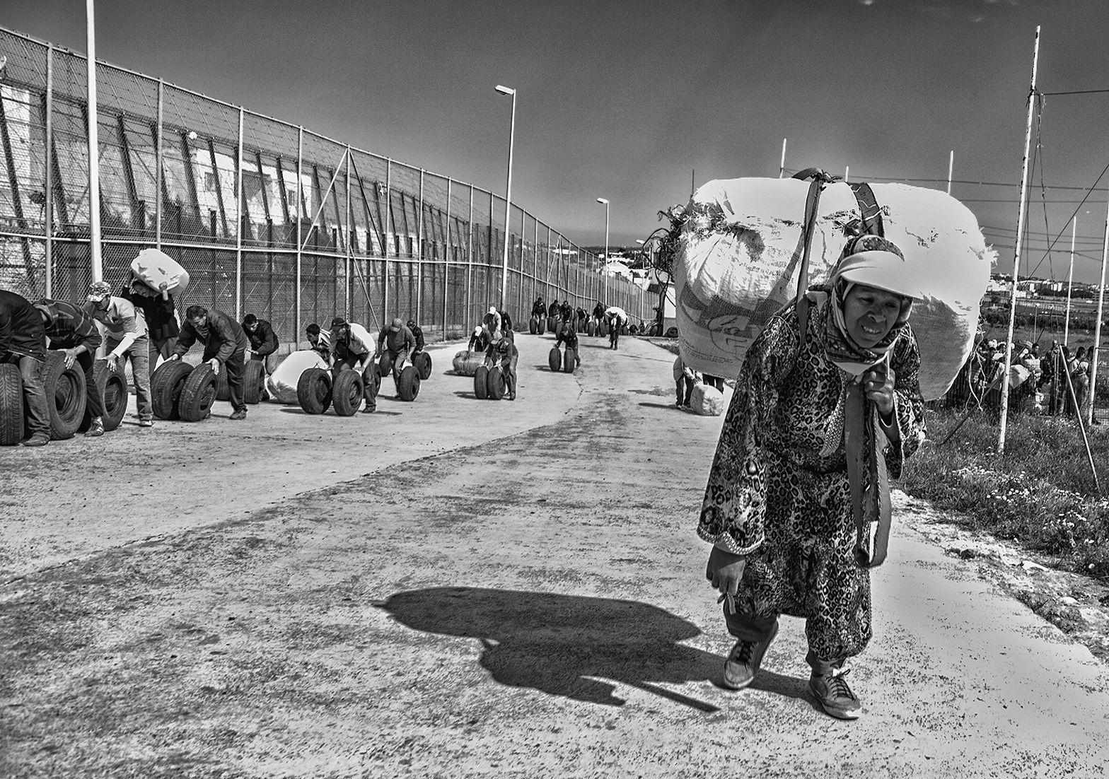 A woman walks towards the border with a heavy pack on her back, while a group of men push tires. Melilla. Spain