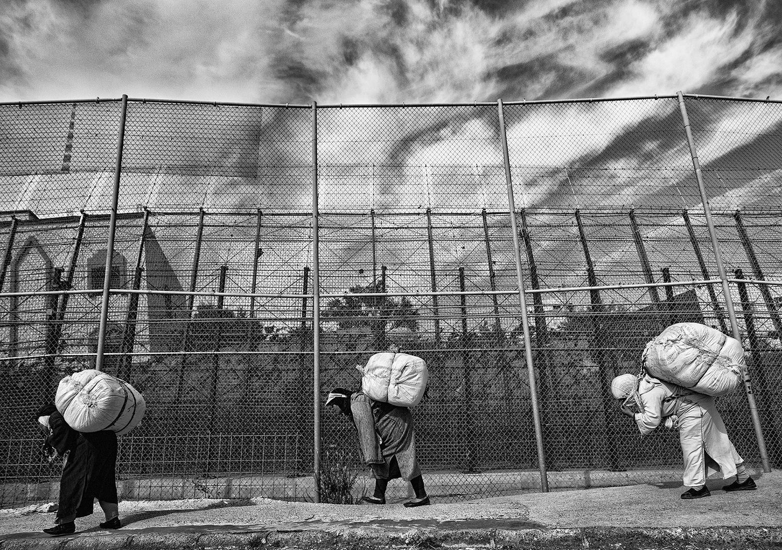 Three women bend their bodies forward because of the heavy goods loaded in their back. They walk towards the border between Spain and Morocco. Melilla. Spain