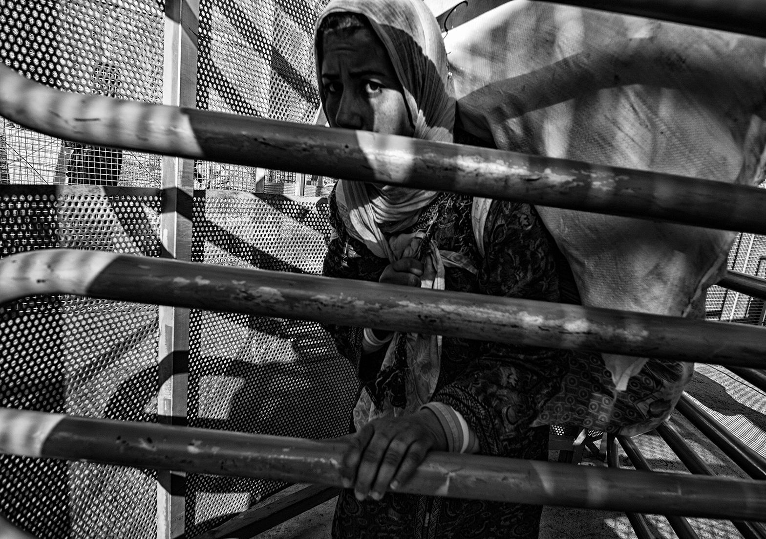 A woman crosses the border turnstiles. Moroccans have to go through narrow turnstiles and have to wait for hours. The border has not been designed for such a flow of people. Melilla. Spain